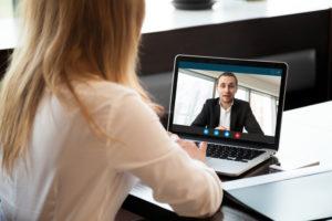 Frau videotelefoniert mit einem Mann über den Laptop.