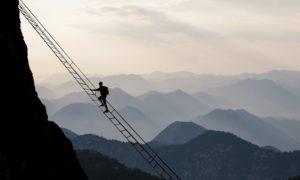 Mutiger Wanderer klettert über eine hohe Seilleiter über die Bergkette.