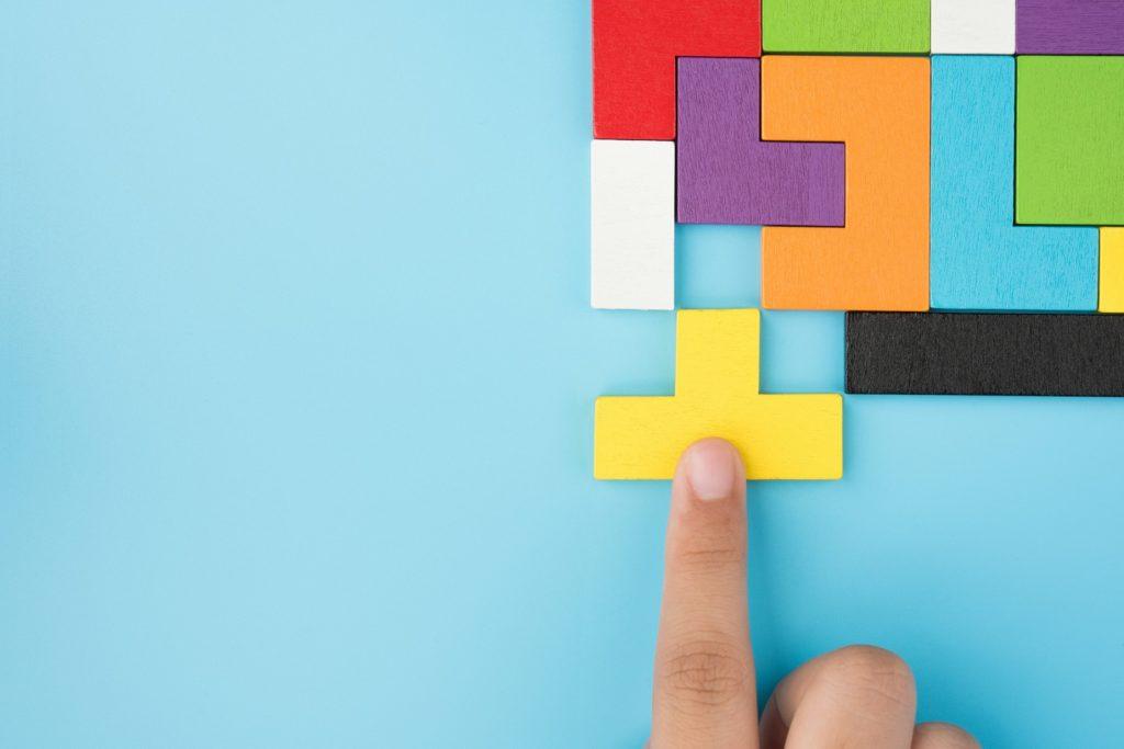 Ein buntes Tetrispuzzel und ein Zeigefinger.