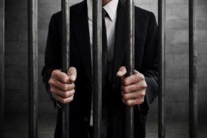 Mann hinter Gitterstäben (Gefängnis).