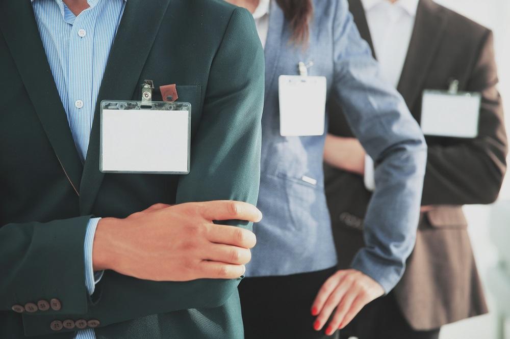 Adrett gekleidete UnternehmerInnen mit Besucherschild.