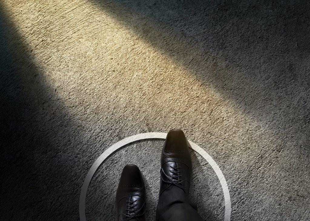Füße auf dem Aphalt, die von einem Kreis eingekreist sind.
