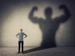 Mann steht vor seinem eigenen muskelbepackten Schatten.